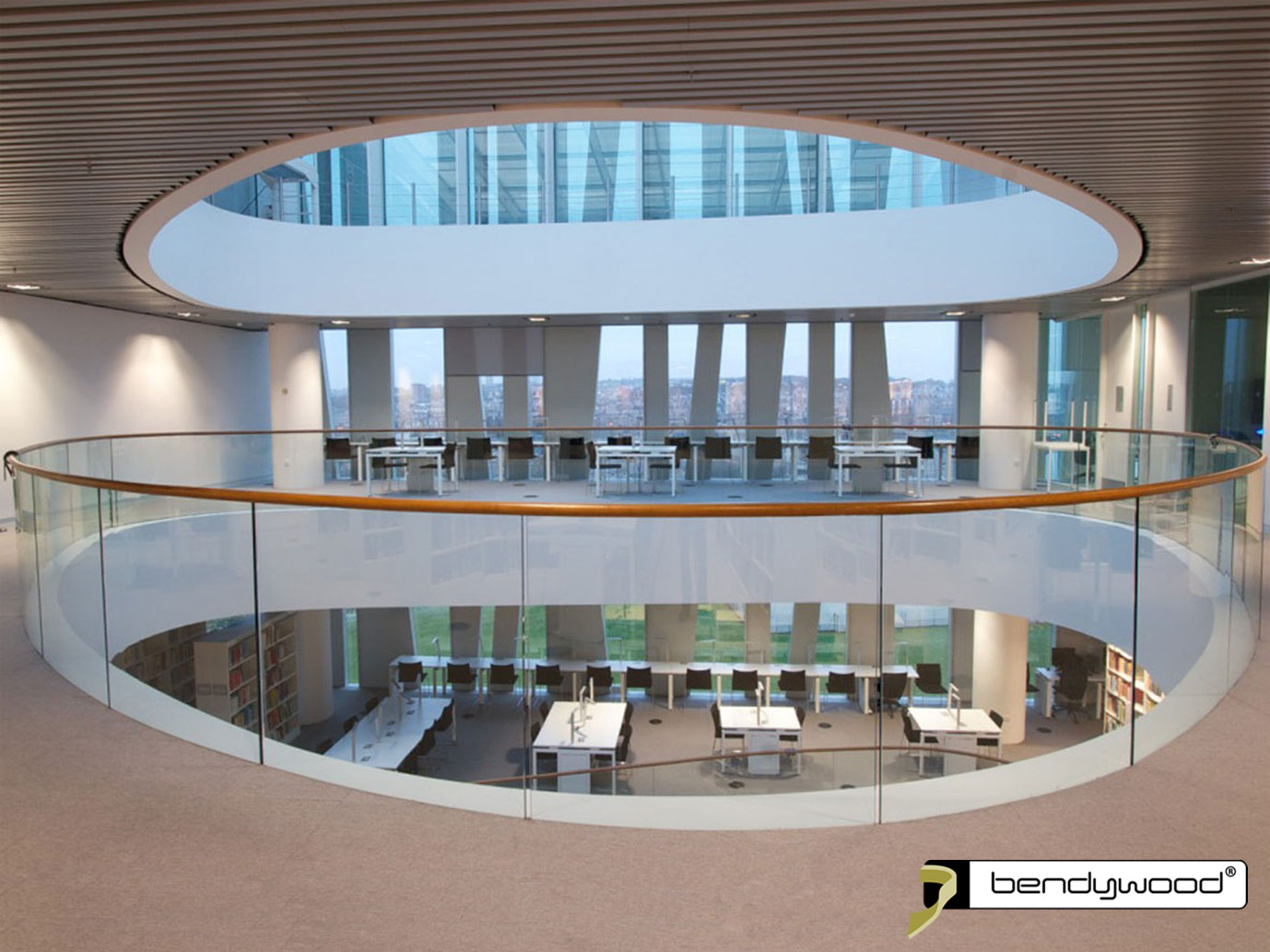 Round bending handrails in Bendywood®-oak, bent and fitted directly onto a glass balustrade